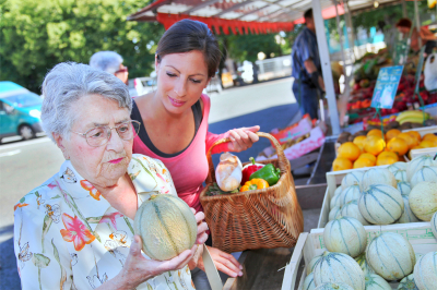 caregiver helping an old woman with shopping