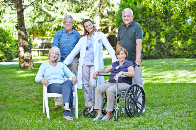 group of senior people in retirement home garden with nurse